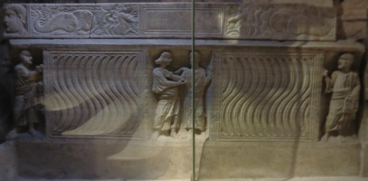 Maximins sarkofag, romersk sarkofag fra 300-tallet, en av de eldste i Frankrike, i krypten i basilikaen Sainte-Madeleine i Saint-Maximin-la-Sainte-Baume. I midten: (den skjeggløse) Jesus sammen med en bedende mann, som man regner med er Maximin, t.v. Peter (uten nøkkel eller hane), til høyre Paulus med bokrull. ©Joachim Schäfer – Ökumenisches Heiligenlexikon